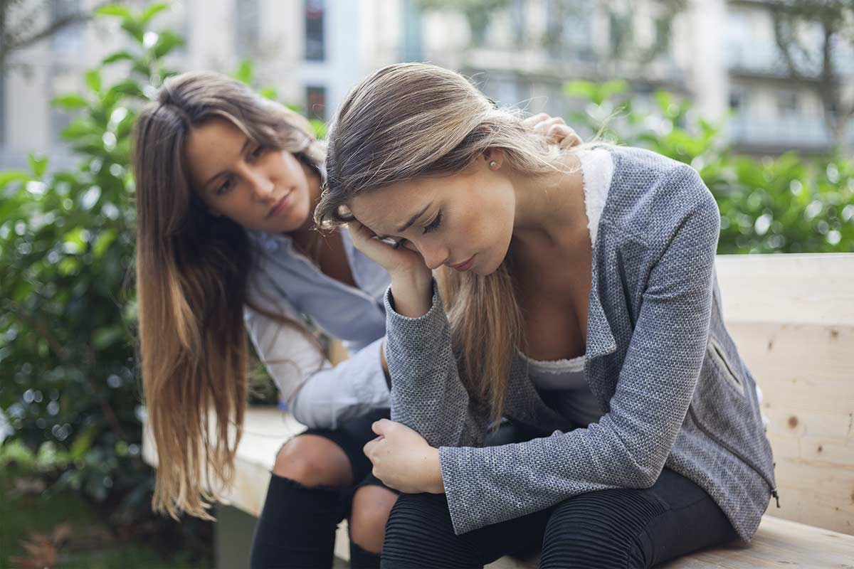 woman helping another woman how to help someone with ptsd
